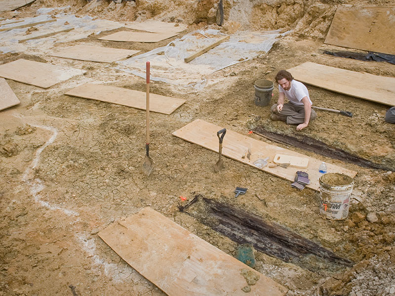 In this file photo from March 2013, Follet removes the soil from the lid of one over 35 graves uncovered during construction.
