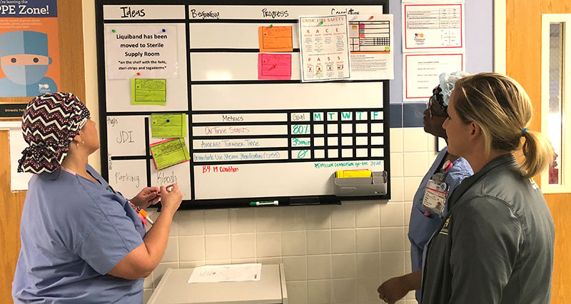 Surgical technician Angela Harrell, nurse Chandry Brown and surgical technician Haley Welch at the visual management board in a surgery ward at Batson Children's Hospital.