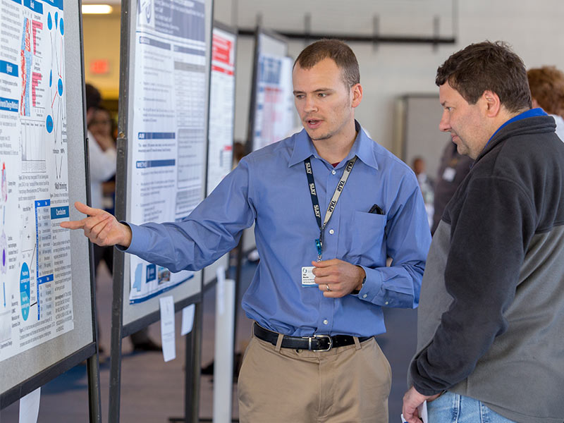 Dr. Alan Mouton, postdoctoral research fellow, discusses his work with Dr. Damian Romero, associate professor of biochemistry, at Department of Medicine Research Day. Mouton won first place for his poster presentation.