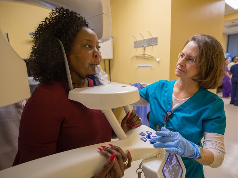Dental assistant Susan Miley takes a radiograph of Johnson's mouth during a recent checkup at UMMC's Oral Oncology Clinic.