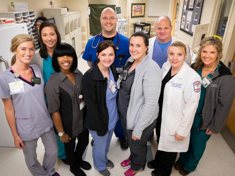 UMMC staff on 5 North include, front row, left to right, registered nurse Molly Ables, housekeeper Tarita Weathersby, nurse graduate Erin Hicks, registered nurse Emily Jones, nurse practitioner LeAnne Adcock, physical therapist Kristin Lang; and back row, left to right, hospital tech Lauren Habig, School of Medicine clinical instructor in orthopedic surgery Brad Martin and registered respiratory therapist Race Robinson. Sneaking a peek (background right) is registered nurse Beth Efrem.