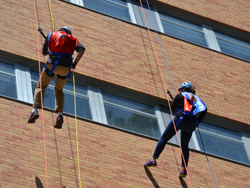 "Funds raised by rappellers, or ""Edgers,"" such as these two are still being totaled, but donations have surpassed the $162,000 mark."