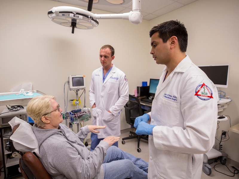 Browning discusses her recovery with Velasco, right, and Dr. Matthew Nimmich, a resident in oral and maxillofacial surgery and pathology.