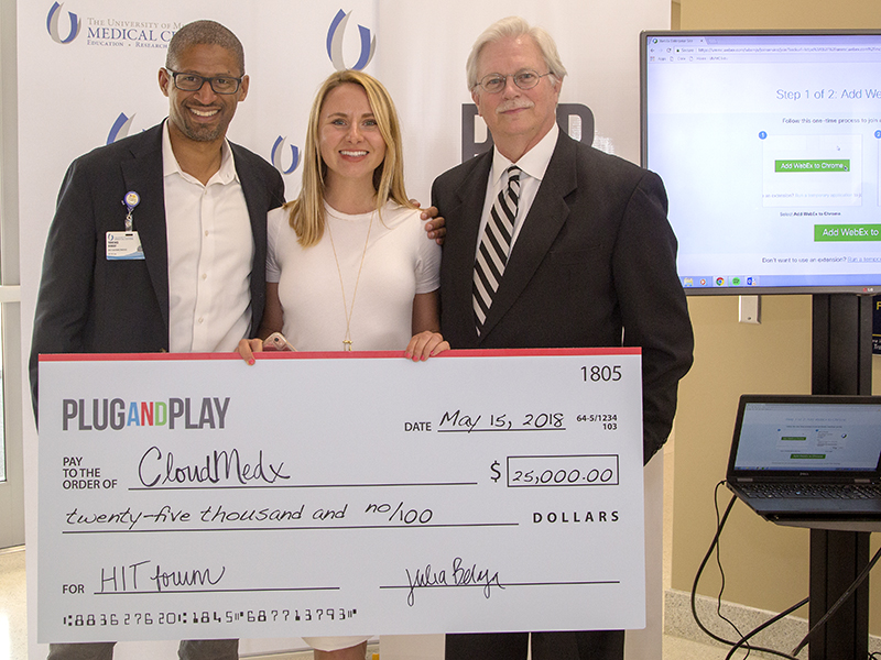 Displaying the check awarded to the pitch competition winner are, from left, Terrence Hibbert, director of innovation; Julia Belaya of event cosponsor Plug and Play; and Dr. Richard L. Summers, associate vice chancellor for research.