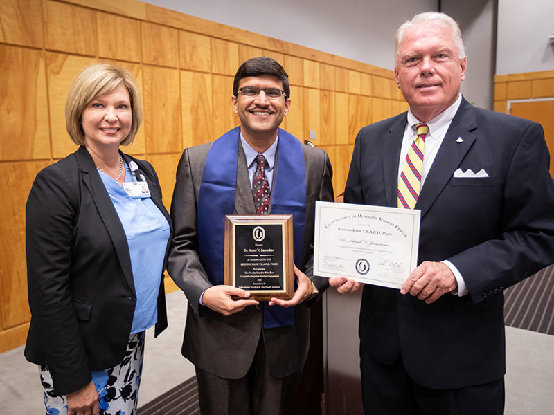 Dr. Amol Janorkar, center, accepts a plaque and certificate pronouncing him recipient of the 2018 Regions TEACH Prize from Dr. LouAnn Woodward, left, vice chancellor for health affairs and dean of the School of Medicine, and Alon Bee, city president-metro Jackson Regions Bank.