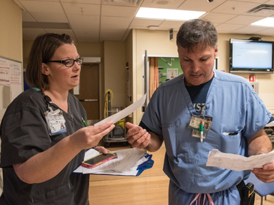 "Kesha Prystupa, a Pediatric ED nurse manager, and Blake Jones, a registered nurse and educator, discuss ""patients on paper"" expected in their area as part of a mass casualty exercise."