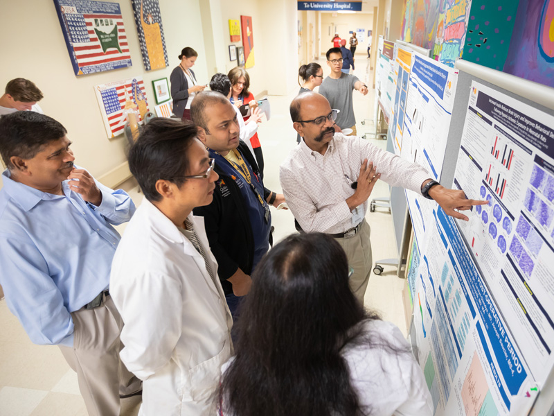 Among those reviewing a research poster are, from left, Dr. Abhay Bhatt, Dr. Yi Pang, Dr. Chirag Talati, Dr. Sumara Ramararo and Dr. Pradeep Alur.