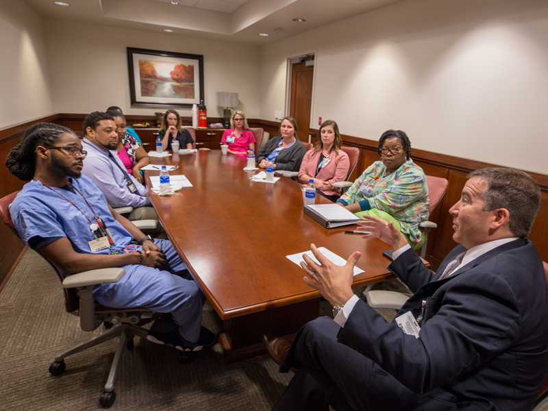 Kevin Cook, right, CEO of the Health System, fields questions from selected employees during a monthly