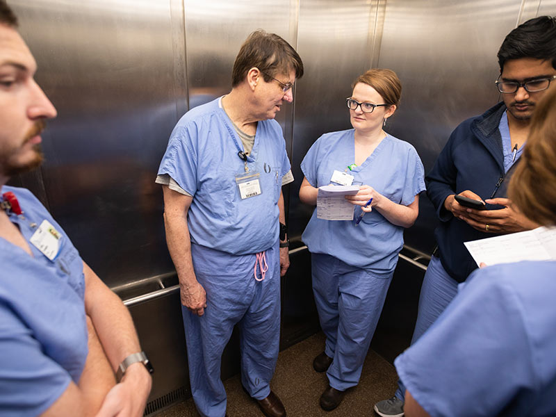Dr. Meagan Mahoney, center right, general surgery resident, grabs an elevator conversation with Dr. Larry Martin, UMMC professor of surgery and trauma surgeon.