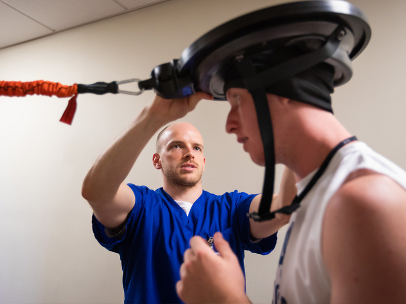Tyler Luchtefeld, a physical therapy resident, affixes a device to soccer player Cameron Allcorn's head to test reflexes and motor skills.