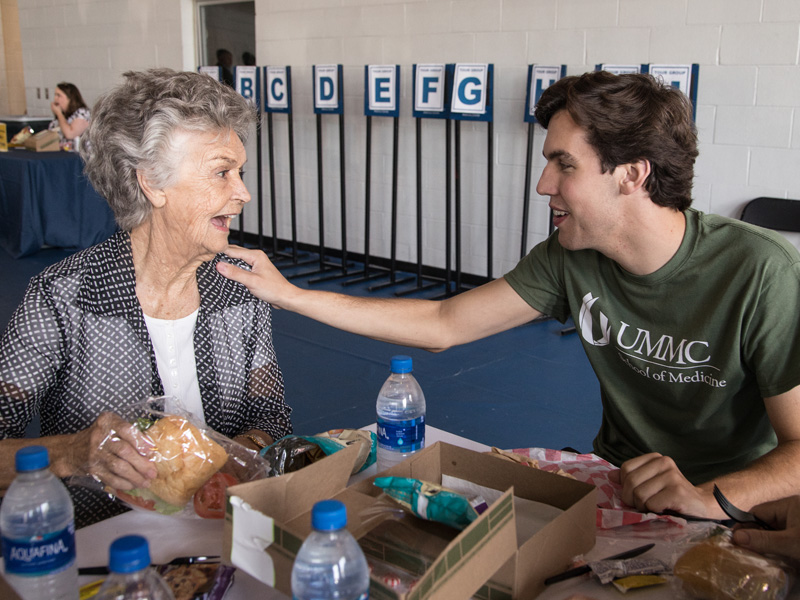 During Family Day lunch in the Student Union Gym, first-year medical student Alexander Knight shares a touching moment with his grandmother Helen Knight of Laurel.