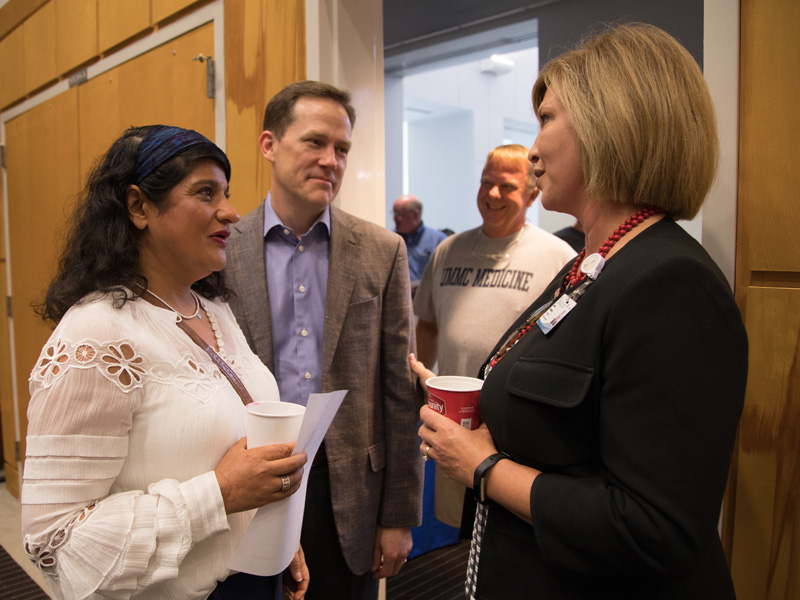 Dr. LouAnn Woodward, right, vice chancellor for health affairs and dean of the School of Medicine, greets Ray and Monica Harrigill during their Family Day visit to support first-year student Manish Harrigill.