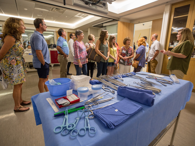 Students, family and friends tour an operating room in the simulation suite.