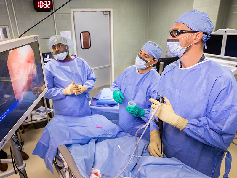 Dr. Michal Senitko, right, performs a medical thoracoscopy on patient Wayne Simpson in coordination with Dr. James T. Williams, left, and Dr. Trey Abraham,