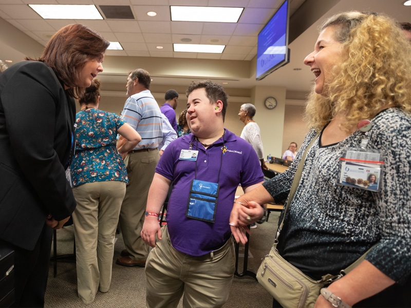 Rankin County school district transition instructor Jennifer Jackson, left, welcomes Wesley Tyson, son of UMMC nursing supervisor Lori Tyson, right, to the Project SEARCH program at the Medical Center.