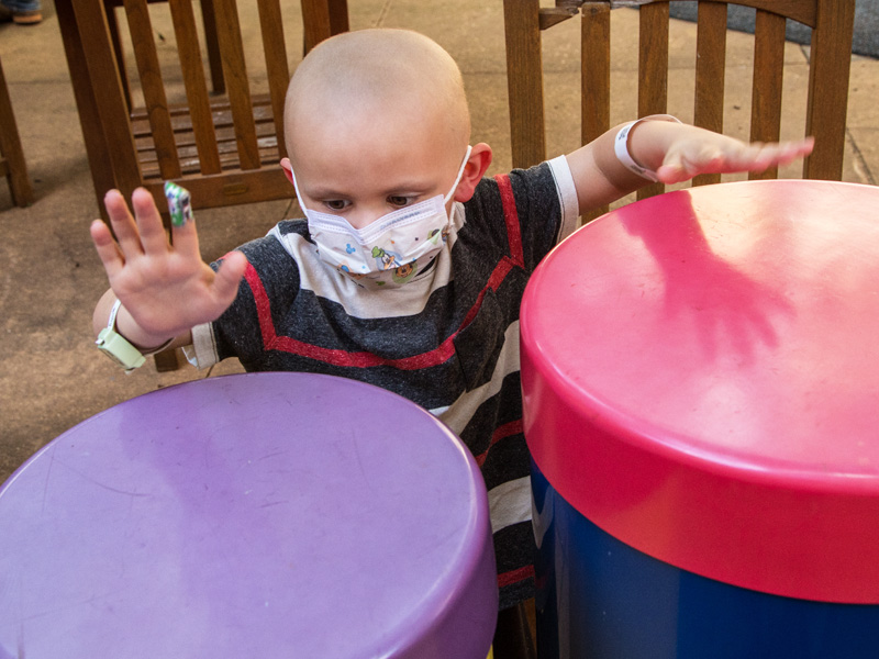 Batson Children's Hospital patient Harlan Harper of Sandy Hook plays the drums in the Rainbow Garden.