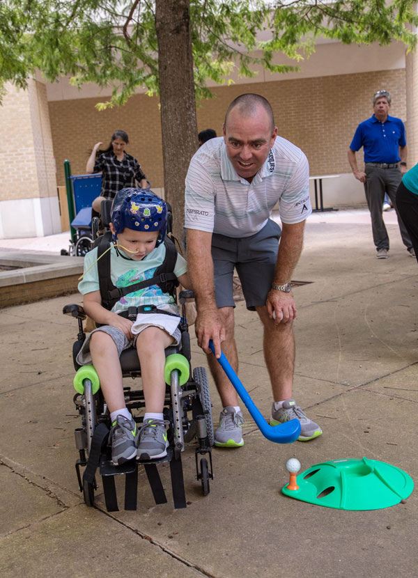 Batson Children's Hospital patient Peyton Homan of Greenville gets a lesson from PGA TOUR golfer Ryan Armour.