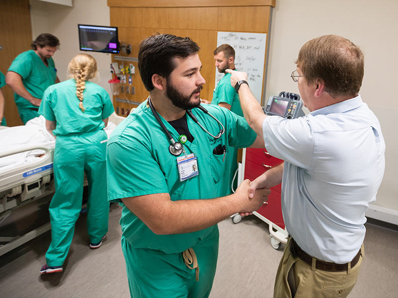 "Dr. Dustin ""Dusty"" Bratton, left, calms down a patient's relative -- portrayed here by Orledge."