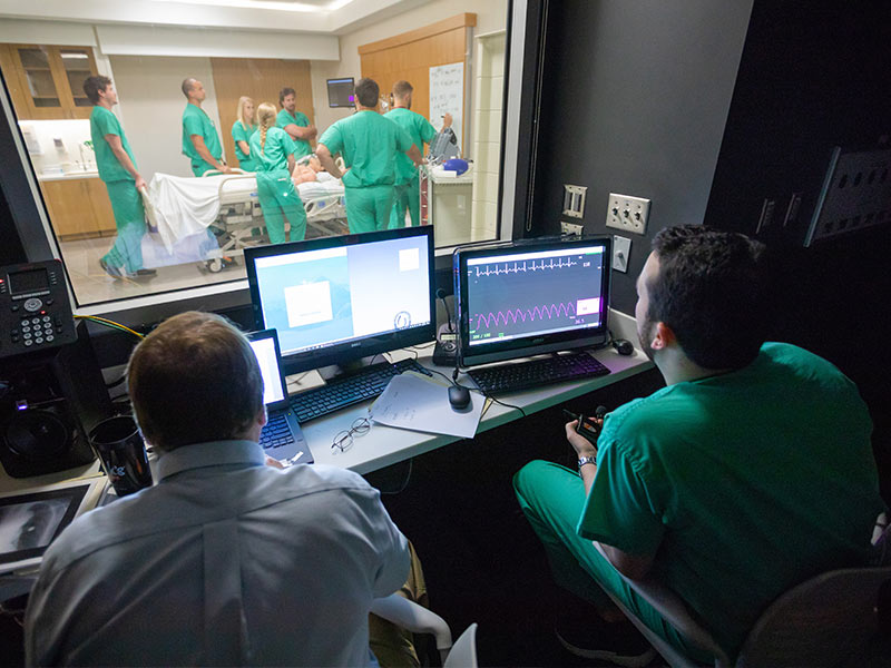Dr. Jeffrey Orledge, left, and Dr. Jeremy Benoit, a third-year resident, manipulate vital statistics for the simulated patient being observed by a group of Emergency Medicine interns.