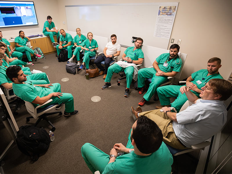 Orledge, right, conducts a debriefing session with Emergency Medicine residents.