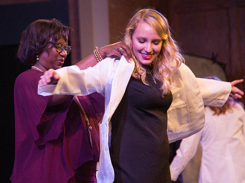 Dr. Loretta Jackson-Williams, professor of medicine and vice dean for medical education, helps first-year medical student Anna Margaret McDonnell slip into her coat during the Aug. 9 White Coat Ceremony.