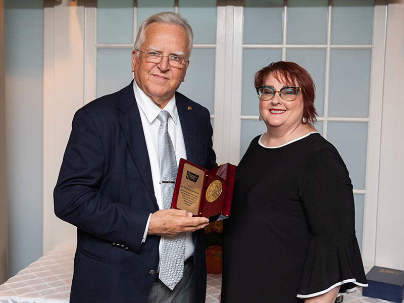 Letitia Thompson, right, vice president of cancer control for the American Cancer Society's South Region, presents Dr. John Ruckdeschel, UMMC Cancer Institute director, with the society's St. George Award during a reception Thursday in Jackson.