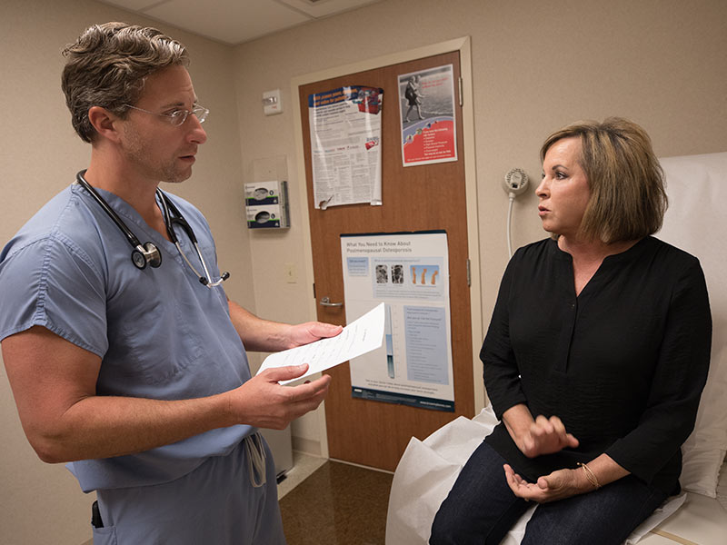 Dr. John Winscott, associate professor of cardiology, and Kim Moore of Flowood discuss her progress following Moore's June 1 heart attack.