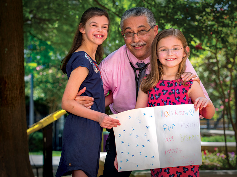 Dr. Makram Ebeid smiles with his patient, Sydney Mead of Madison, left, and her little sister, Sophie.