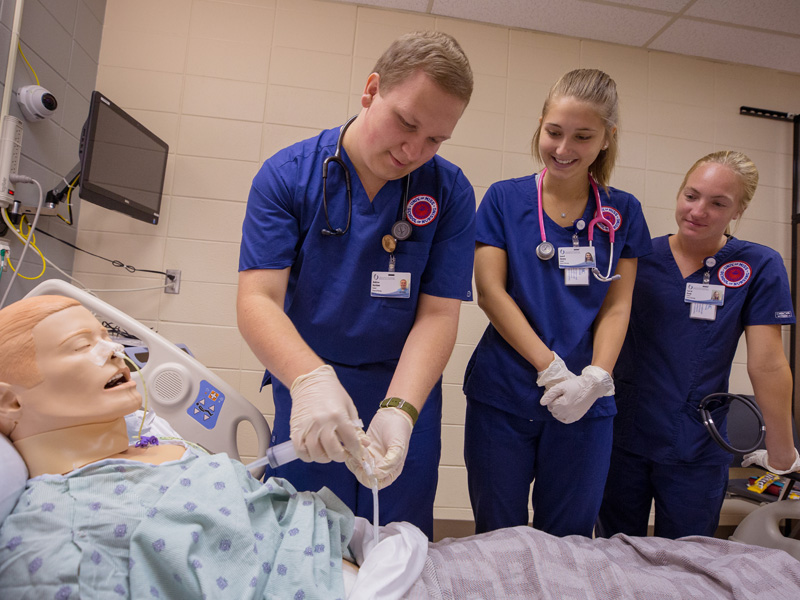 Third-year nursing student Andrew Ketchum, left, prepares to aspirate a simulation mannequin's stomach contents through a gastrostomy tube with classmates Laurel Gurney, center, and Corryl Kemp.