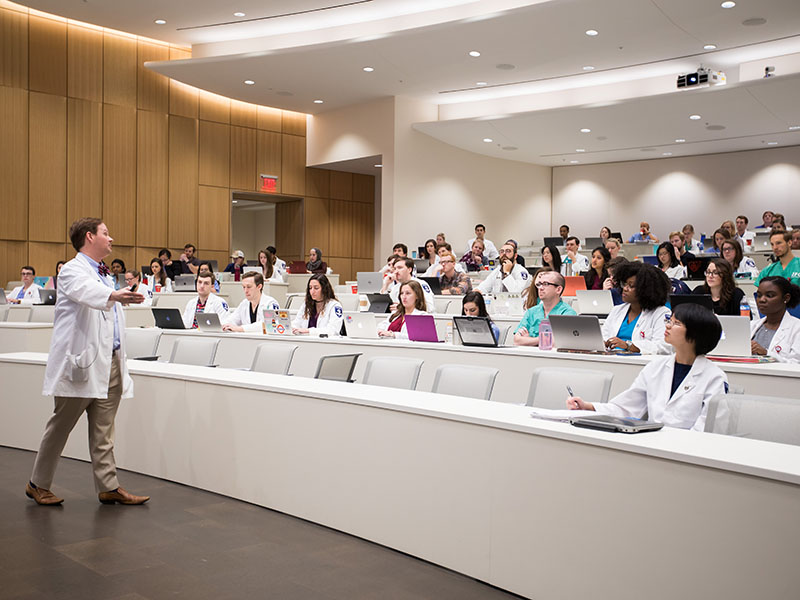 Dr. David Norris, associate professor of family medicine, teaches students in a medical education building amphitheatre.