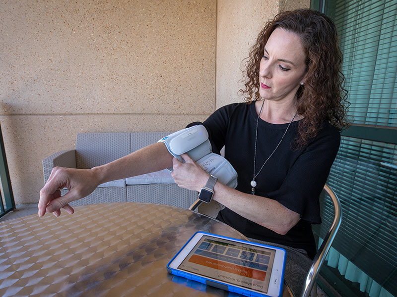 Tanya Tucker, R.N., an educator in the UMMC Center for Telehealth, demonstrates how patients can record their blood pressure from home.