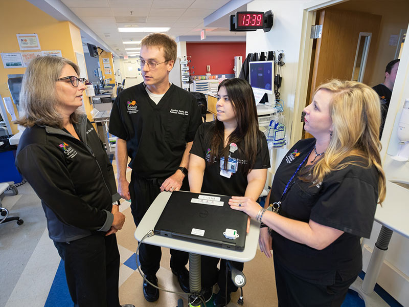 Dr. Elizabeth Christ, left, professor of pediatric critical care, talks with, from left, Dr. Jonathan Smith, Dr. Marivee Borges Rodriguez and Nikki Mayo, nurse practitioner.