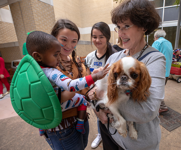 Batson Children's Hospital patient Jayceston Harris of Waynesboro pets therapy dog Ollie, held by owner Cynthia Jones of Brandon.