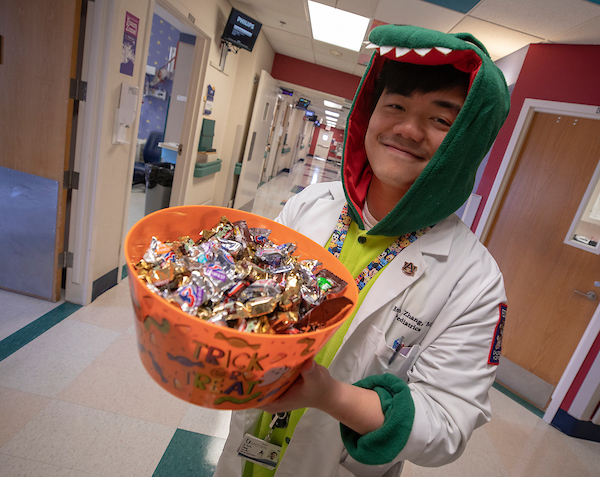 Pediatric resident Dr. Kevin Zhang shows some of the Halloween treats on the fifth floor of Batson Children's Hospital.