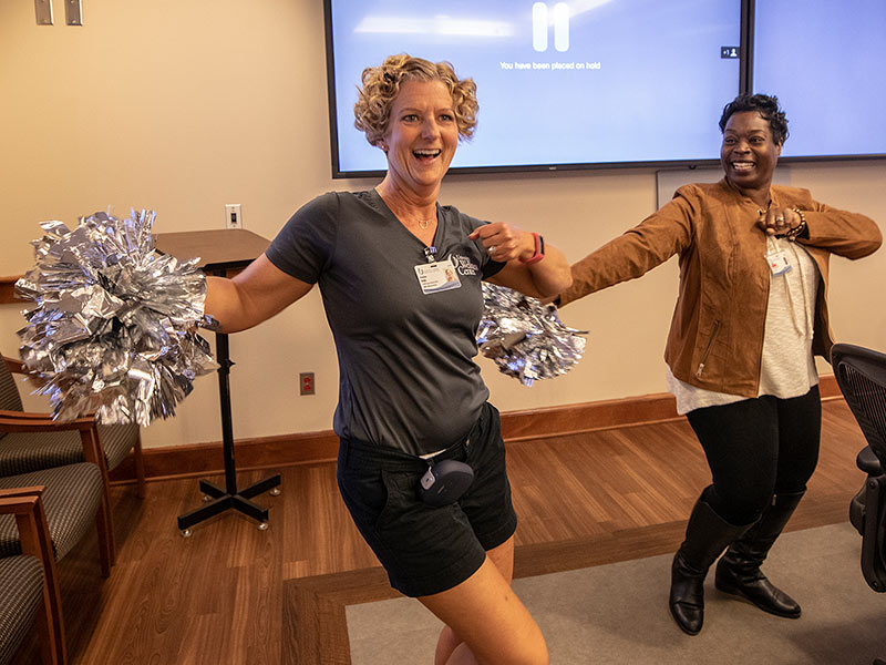 Heather Biddle, left, University Wellness coordinator for group exercise and safety, and Josilind Martin-White, Office of Patient Experience customer service representative, stretch their muscles to music during a recent