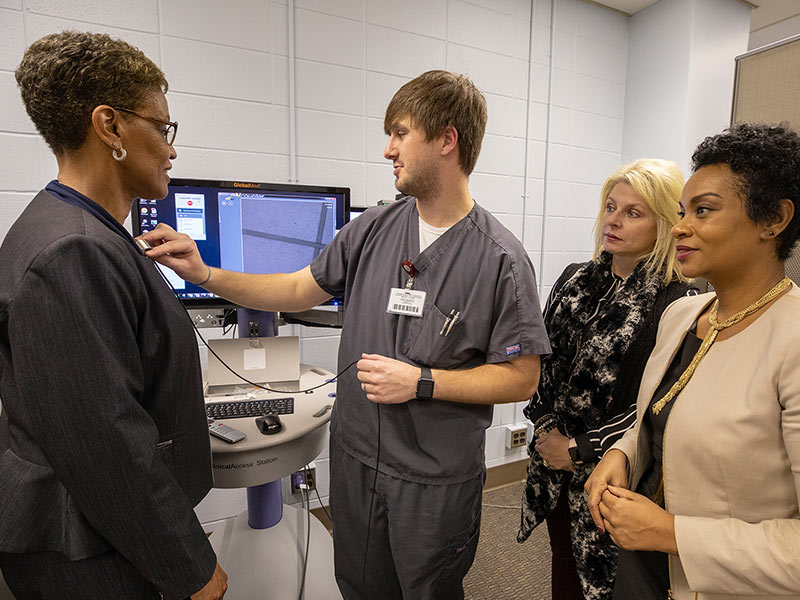John Farr, nurse practitioner and School of Nursing instructor, explains some of the gadgets used in telemedicine to Mississippi Board of Nursing members. From left, Executive Director Phyllis Johnson, General Counsel Brett Thompson and CFO Shan Montgomery listen to Farr.