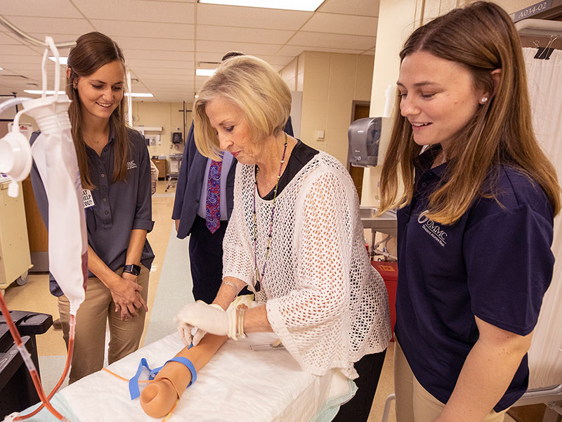 Becky Tustain practices starting an IV in the simulation lab with nursing students Kathryn Dooley, left, and Katie French, right.