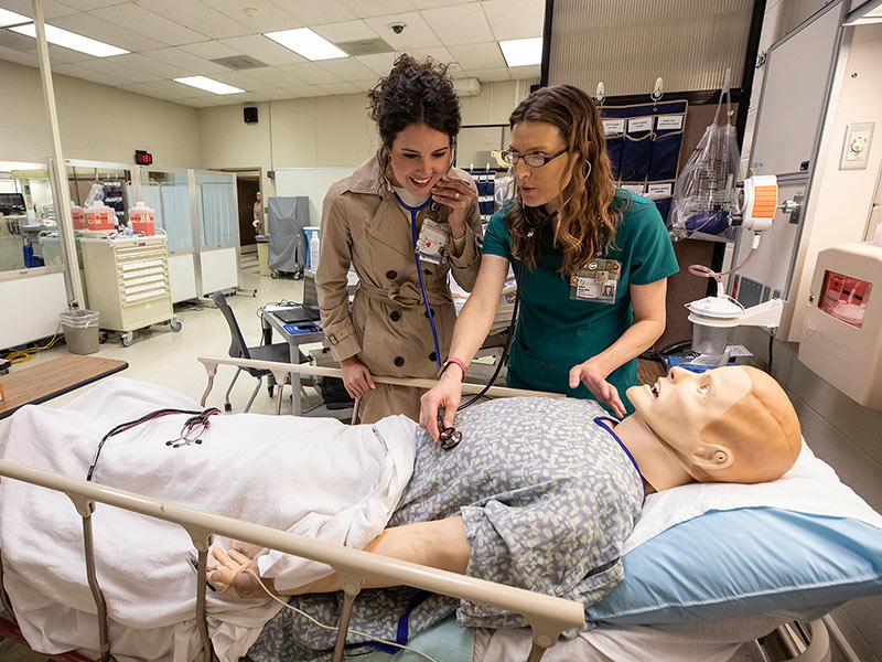 School of Nursing alumna Presly Lowry, left, RN, CICU, checks out the new and improved high fidelity simulator with instructor Melissa Klamm.