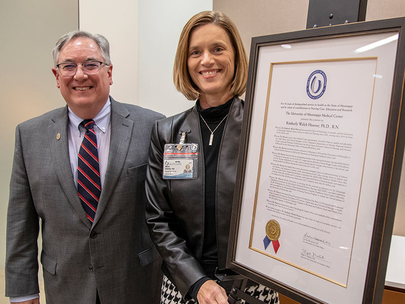 Dr. Kim Hoover receives a citation for her 30 years of distinguished service to health care in Mississippi from Dr. Ralph Didlake.