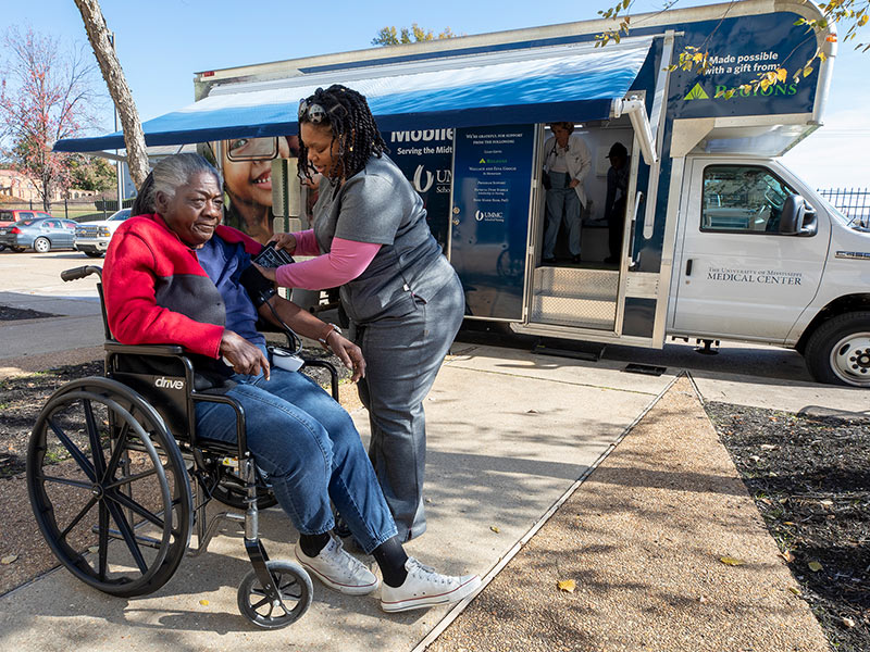 Betty Moore, Jackson Manor resident, gets her blood pressure checked by Micha'el Sheriff, patient care technician, in front of the UNACARE mobile clinic.