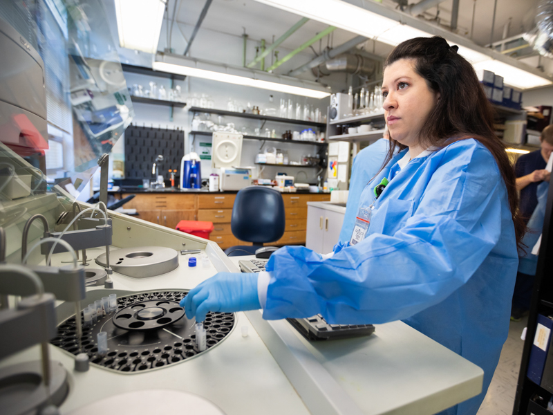 Alana Saldana, medical technologist, loads patient samples into a general chemistry analyzer for drug testing to detect compounds, including powerful opioids.