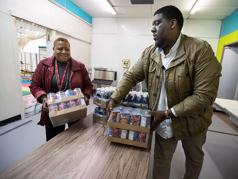 Beneta Burt, president and CEO of the Mississippi Urban League, and UMMC project administrator Darryl Jefferson unload canned goods for shelving at the EversCare Pantry.