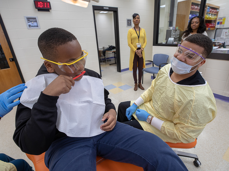 Johnson Elementary School student Darnell Geralds in the foreground shows his tooth brushing technique to dental student Devin Stewart.
