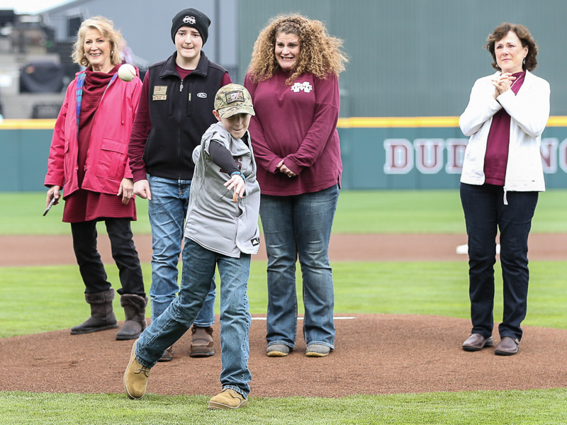 Corbin Connerley throws the first pitch Feb. 22 at a Mississippi State University home game. In the background from the right is Karen Connerley, mother of Jonathan Connerley; his brother Caleb; mom Gena; and Gena's aunt, Cindy Christian.