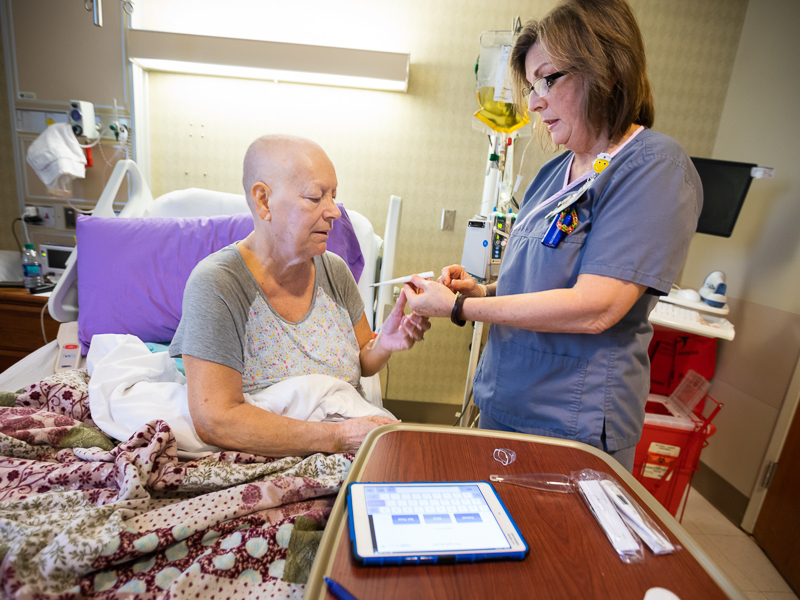 Shirley Crnkovic reviews the equipment she'll take home with Bone Marrow Transplant outpatient nurse Rebecca Smith.