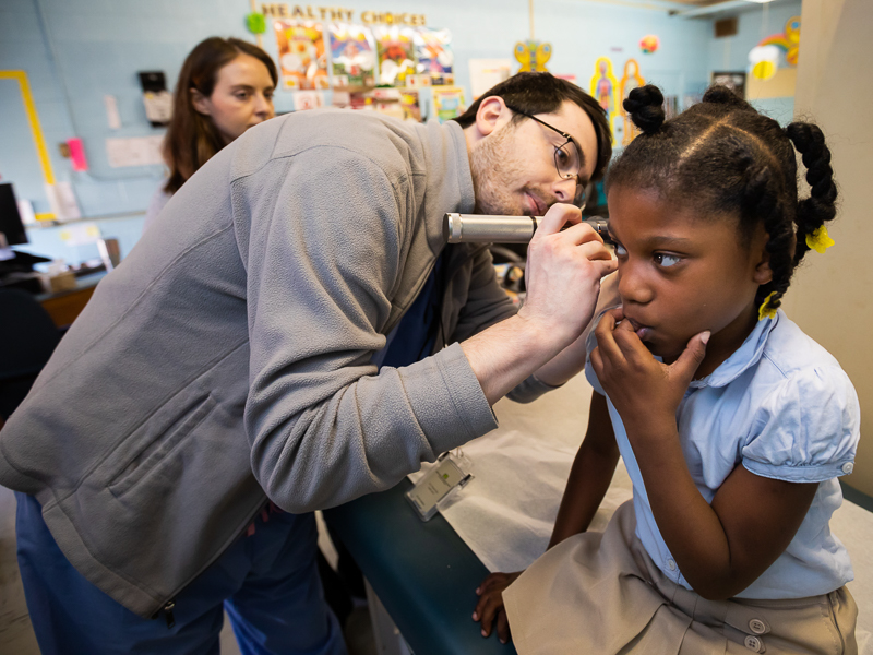 Third-year medical student Brandon Bush examines 1st grader Leilani Gray's right ear as part of a well-child screening.