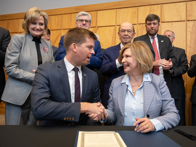 Dr. LouAnn Woodward, UMMC vice chancellor for health affairs and dean of the School of Medicine, shakes hands with Ed Parkinson, acting CEO of the FirstNet Authority, after each signed a memorandum of understanding between the two organizations aimed at improving emergency medical response communication and connectivity in Mississippi, especially in rural areas. Standing behind them are, from left, U.S. Sen. Cindy Hyde-Smith, Gov. Phil Bryant, U.S. Secretary of Commerce Wilbur Ross and Medical Director of the UMMC Mississippi Center of Emergency Services Dr. Damon Darsey.