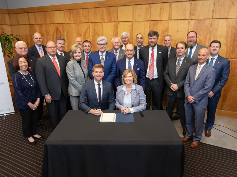 Flanked by board members of the FirstNet Authority and officials with UMMC's Mississippi Center for Emergency Services, Ed Parkinson, acting CEO of the FirstNet Authority, and Dr. LouAnn Woodward, vice chancellor for health affairs and School of Medicine dean, sign a memorandum of understanding between FirstNet and UMMC.
