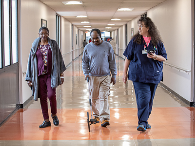 Registered nurse and cardiology care coordinator Stephanie Teague, right, walks with mitral valve patients Julia Ann Flowers and Lucious Thomas.