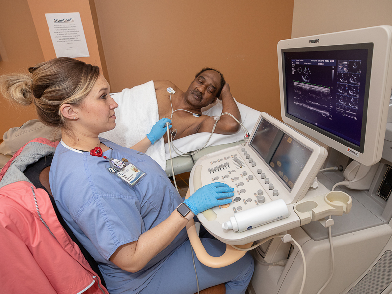 Cardiology sonographer Heather Edgar examines images of the heart of Lucious Thomas, who underwent a procedure to repair his mitral valve in January.